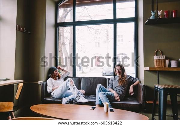 2人の友人がストリートカフェで会い、コーヒーを飲み、時間を過ごし、話し合う。
