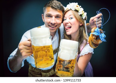 Two friends, men and women, having clinking glasses with Bavarian beer