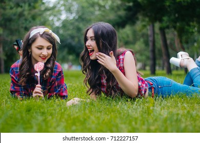 Two friends on a hot summer day lie on a green lawn in the park. Girls with red lips. Communication with a friend. Have fun