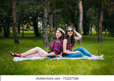 Two friends on a hot summer day are sitting on a green lawn in the park. Girls with red lips. Communication with a friend. Have fun