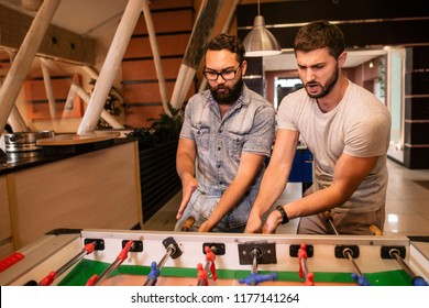 Two friends play table football in a bar