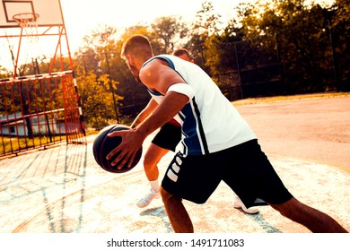 Two friends playing basketball on court outdoors at sunset.