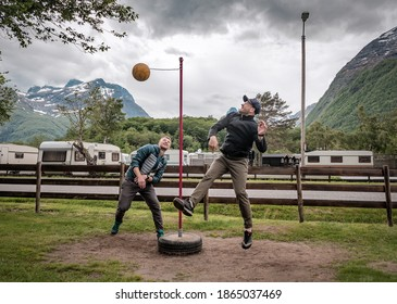 two friends are playing tetherball at campsite