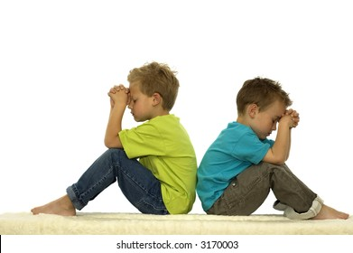 Two friends are praying while sitting with their backs against each other.