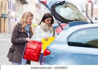 Two friends putting a shopping bags in the car