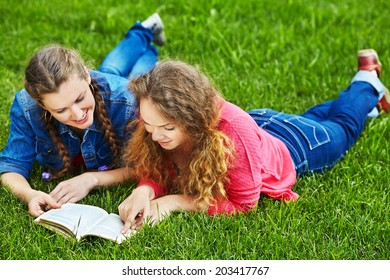 Two friends reading a book or studying while lying on the grass in the summer park. Youth lifestyle.