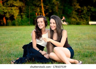 Two friends relaxing outside in park and pointing at something