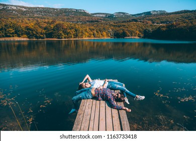 Two friends resting on peer and enjoying lake view in autumn. Good sunny day for resting outdoors and travel.