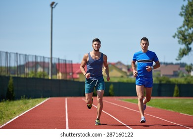 Two friends running on the lines at the stadium in a sunny day