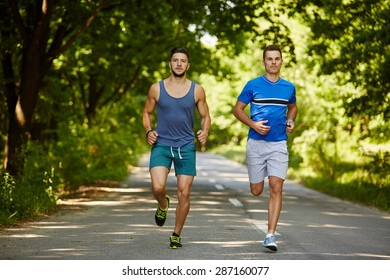 Two friends running through the forest on a jogging trail