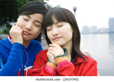 Two friends sharing earphones, eyes closed