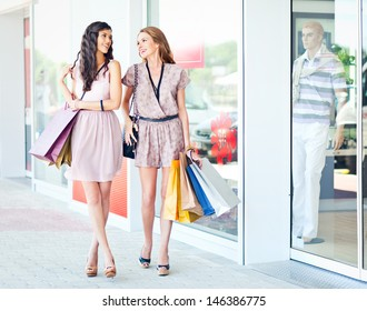 Two friends shopping together and talking.