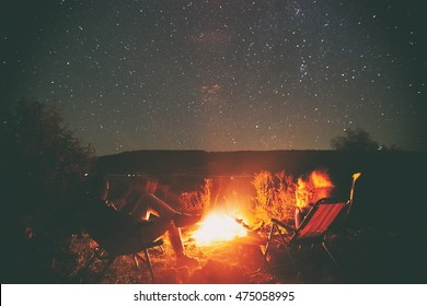 Two friends are sitting around a campfire and just relaxing