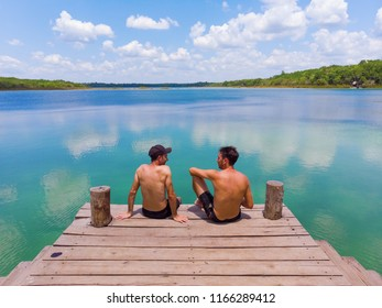 Two friends sitting by a freshwater lagoon, Quintana Roo, Mexico