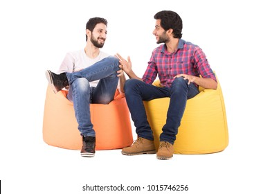 Two friends sitting on beanbags talking, smiling, looking happy, isolated on a white background.