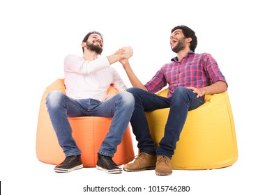Two friends sitting on beanbags jocking, laughing happily, hitting their hands together, isolated on a white background.