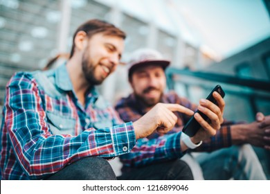 Two friends sitting on football stadium steps and making bets using gambling mobile application. Men watching online broadcast waiting for winner results. Focus is on hand with mobile phone