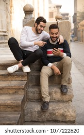 Two friends sitting on the stairs in an ancient street looking at the phone together one pointing at the screen smiling.