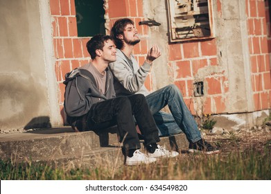 Two friends sitting on stairs and smoking cannabis or hashish joint in abandoned ghetto part of the city