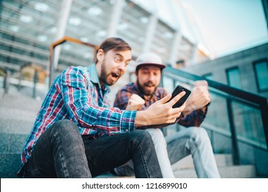 Two friends sitting on steps near football stadium and enjoying success of bet winning in a gambling mobile application. Focus is on hand with mobile phone.