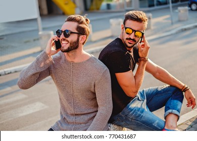 Two friends sitting in the street, talking on the phone. One is happy and one is sad