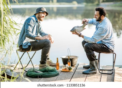 Two friends sitting together with beer and fish on the picnic while fishing near the lake