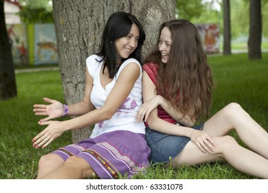two friends sitting under tree