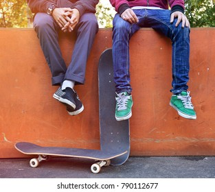 Two friends skateboarders in the skatepark rest after skating