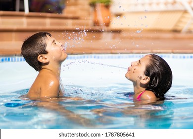 Two friends spitting water from mouth in a pool