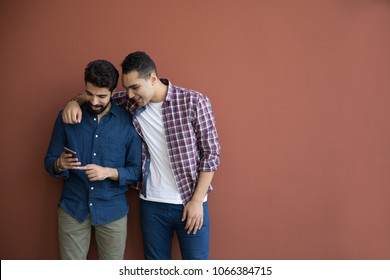 Two friends standing against the wall looking at the phone together, one putting his arm on the shoulder of his friend.