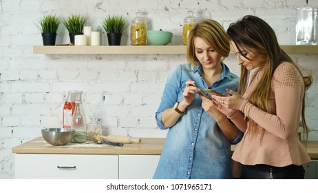 Two friends are standing in the kitchen with cell phones. They are looking for a recipe for food on the Internet.