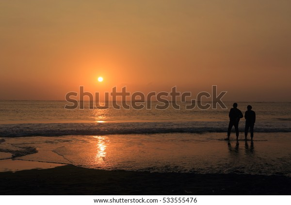 two friends in the sunset beach in a winter evening
