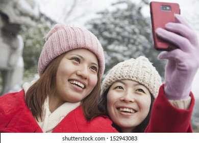 Two friends taking picture with cell phone in snow