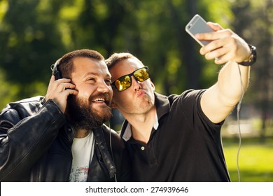 Two friends taking a selfie photo with mobile smart phone in nature, listening to music with headphones