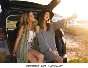 Two friends taking a selfie while sitting in the trunk of a car