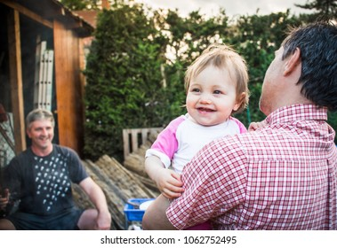 Two friends talking at the BBQ garden party - father with his cute one-year-old daughter laughing over his shoulder. Sweet little baby girl toddler on men's summer business - meat grilling - backdrop