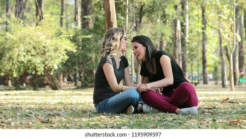 Two friends talking to each other at the park. Candid conversation between two girlfriends speaking exchanging ideas and gossip