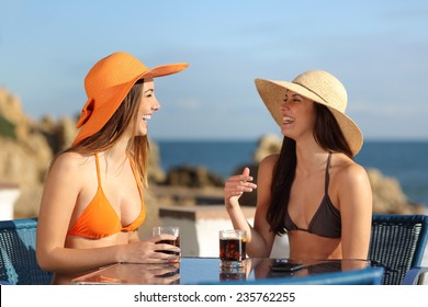 Two friends talking in an hotel terrace on holidays with the beach in the background