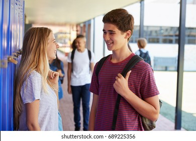 Two friends talking in school corridor at break time