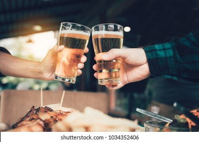 Two friends toasting and clinking with glass of beer.