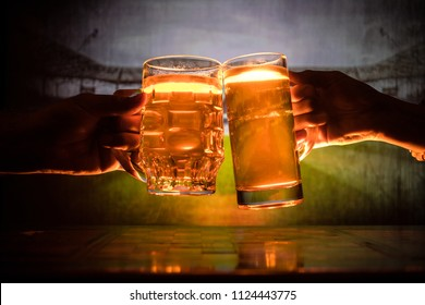 Two friends toasting (clinking) with glasses of light beer at the pub. Beautiful background with blurred view of playing game at the stadium. Selective focus