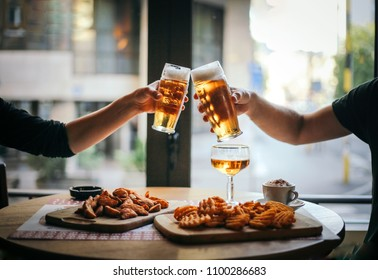 Two friends toasting with glasses of light beer at the pub.