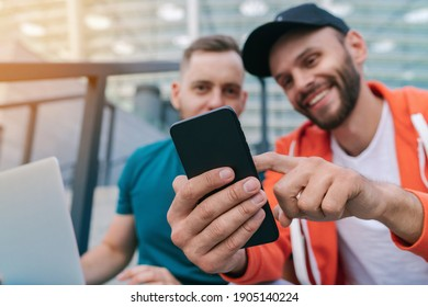 Two friends using mobile phone and laptop for betting during soccer play ready to celebrate victory of favourite team. Men using gambling application while sitting on stadium steps. Focus is on hand.