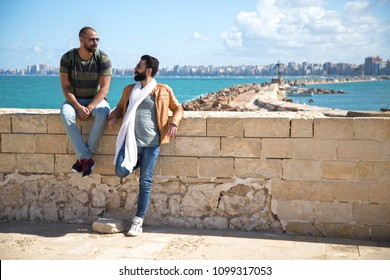 Two friends visiting Alexandria city one of them sitting on a stone fence and the other one standing, they have a good conversation
