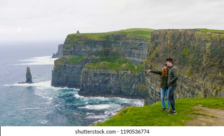 Two friends walk along the Cliffs of Moher