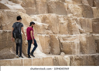 Two friends walking goes down from the huge stone of the pyramid.