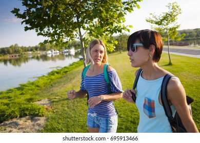 Two friends walking in the park. Girls actively spend time in nature. The women are talking.