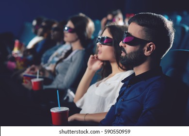 Two friends watching movie in 3d glasses.
