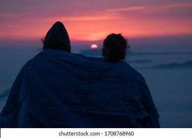 Two friends watching the sunrise on the top of the mountains, above a sea of clouds. Covered by a sleeping bag. Photo of Valle de Mena, Burgos. Mountains of Vasc Country, North of Spain. - Shutterstock ID 1708768960
