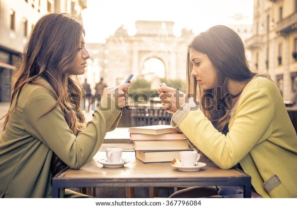 Two friends watching their smart phone while sitting in a cafe. Social concept about new technology people addiction